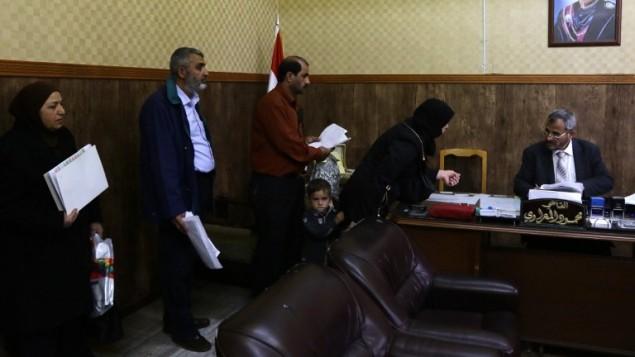 سوريون في مكتب القاضي الشرعي الاول محمود المعراوي الذي يشرف على مسائل الاحوال الشخصية، مثل الطلاق او الزواج الثاني، في دمشق، 8 مارس 2016 (AFP PHOTO / LOUAI BESHARA)