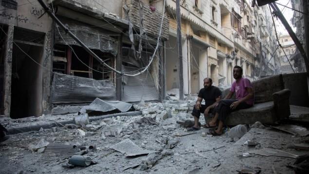 سوريون يجلسون ويتفحصون الحطام بعد غارة جوية في حي يقع تحت سيطرة المعارضة في مدينة حلب السورية، 18 سبتمبر 2016 (AFP/Karam al-Masri)