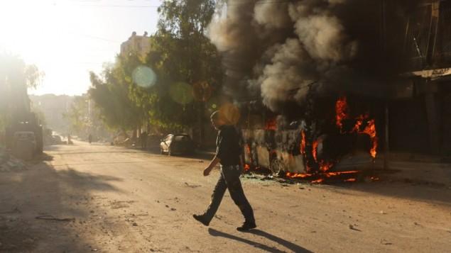 رجل سوري يمر امام حافلة مشتعلة بعد غارات جوية في شرق حلب، 25 سبتمبر 2016 (AFP/AMEER ALHALBI)