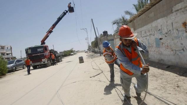 عمال من شركة الكهرباء الفلسطينية يقومون بسحب خط كهرباء، تدمر الكثير منها في أعقاب غارة إسرائيلية في رفح جنوبي القطاع، 6 أغسطس، 2014. (photo credit: AFP/SAID KHATIB)