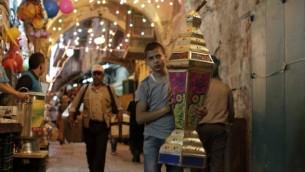 صورة توضيحية: طفل فلسطيين يحمل فانوسا يمر أمام محلات تجارية في البلدة القديمة بالقدس في 16 يونيو، 2015. (AFP PHOTO/AHMAD GHARABLI)