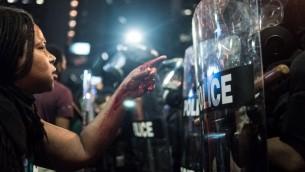 امرأة تغطي يداها الدماء امام عناصر الشرطة خلال مظاهرات في شارلوت، كارولاينا الشمالية، 21 سبتمبر 2016 (Sean Rayford/Getty Images/AFP)