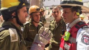 مندوبون من وحدة البحث والانقاذ في قيادة الجبهة الداخلية يتحدثون مع مدير قسم الاطفاء المحلي ايال كاسبي في مكان انهيار موقع بناء بحب رمات هحيال في تل ابيب، 5 سبتمبر 2016 (IDF Spokesperson's Unit)