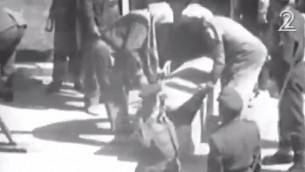 صورة شاشة من تصوير صدر مؤخرا يظهر الجاسوس الإسرائيلي ايلي كوهن يوضع داخل تابوت بعد اعدامه شنقا في دمشق، 18 مايو 1965 (Screenshot/Channel 2)
