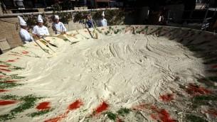 عمال  في مطعم 'أبو غوش' يقومون بإعداد صحن حمص بوزن 4 طن لتسجيل رقم قياسي عالمي في كتاب 'غينيس' في 2010. (Yossi Zamir/Flash90)