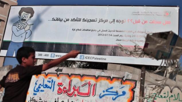 فتى فلسطيني يقف إلى جانب لوحة إنتخابات في غزة. (Wissam Nassar/Flash90)