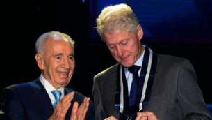 """الرئيس شمعون بيريس يمنح الرئيس الأمريكي الأسبق بيل كلينتون """"الوسام الرئاسي للتميز""""، الأربعاء، 19 يونيو، 2013. (Moshe Milner/GPO/Flash90)"""
