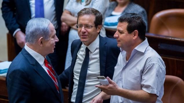 رئيس الوزراء بنيامين نتنياهو يتحدث مع رئيس المعسكر الصهيوني يتسحاك هرتسوغ وزعيم القائمة العربية المستركة ايمن عودة في الكنيست (Yonatan Sindel/Flash90)