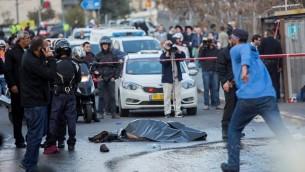 جثة منفذ هجوم فلسطيني ملقاة على الأرض بعد إطلاق النار عليه وقتله بينران عناصر الأمن الإسرائيليين خلال هجوم عند مدخل القدس، 14 ديسمبر، 2015، أدى إلى إصابة 14 شخصا، من بينهم طفل رضيع. (Yonatan Sindel/Flash90)