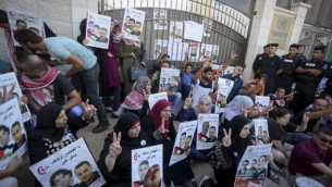 فلسطينيون يحملون لافتات ضد الإعتقال الإداري ودعما للأسرى الفلسطينيين بلال كايد ومحمد ومحمود البلبول أمام مبنى الأمم المتحدة في مدينة رام الله في الضفة الغربية، 22 أغسطس، 2016. (Flash90)
