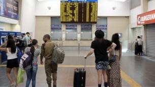 """مسافرون في محطة """"سافيدور"""" المركزية في تل أبيب يتفحصون الجدول الزمني للقطارات، حيث لا تظهر فيه القطارات المتوجهة إلى شمال البلاد، 3 سبتمبر، 2016. (Tomer Neuberg/Flash90)"""