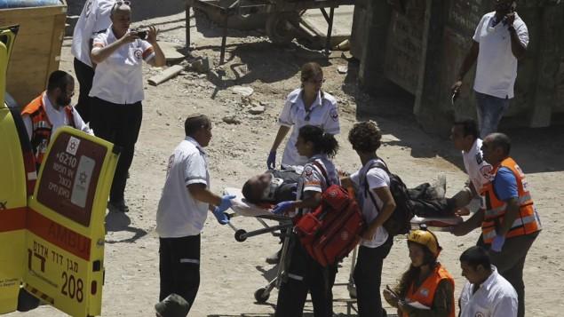 طواقم الإنقاذ تقوم بإخلاء رجل بعد انهيار مبنى في حي رمات هحيال في شمال تل أبيب، 5 سبتمبر، 2016. (Miriam Alster/Flash90)