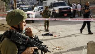 جنود إسرائيليون وقوات أمن في موقع هجوم طعن في مدينة الخليل بالضفة الغربية، 17 سبتمبر، 2016. (Wisam Hashlamoun/Flash90)