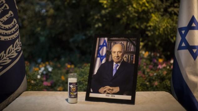 صورة مؤطرة للرئيس الإسرائيلي السابق شمعون بيريس معروضة مع شمعة تذكارية عند مدخل بيت رئيس الدولة في القدس، 28 سبتمبر، 2016. (Hadas Parushl/Flash90)