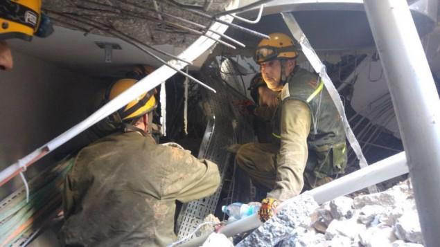عناصر قيادة الجبهة الداخلية في الجيش الإسرائيلي يحاولون العثور على الاشخاص العالقين تحت الركام بعد انهيار موقف سيارات في شمال تل ابيب، 5 سبتمبر 2016 (IDF Spokesperson's Unit)