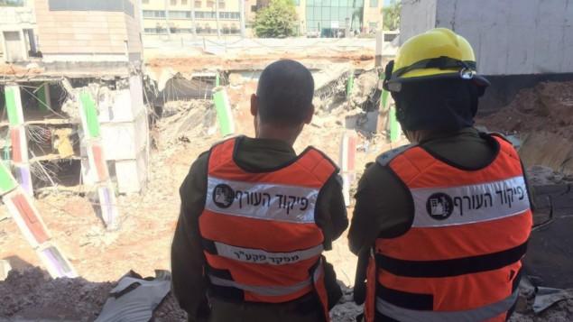 رئيس قيادة الجبهة الداخلية في الجيش الإسرائيلي الجنرال يوؤيل ستريك، يسار، والعقيد يوسي بينتو من وحدة البحث والانقاذ والطنية، يتفحصان الاضرار في موقع انهيار موقف سيارات في شمال تل ابيب، 5 سبتمبر 2016 (IDF Spokesperson's Unit)