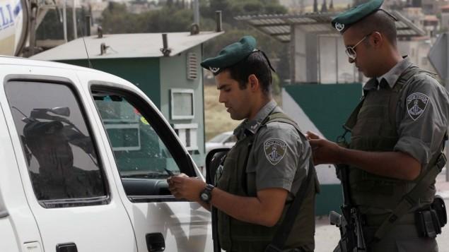 صورة توضيحية لشرطيين من حرس الحدود يقومون بفحص الأوراق الثبوتية لسائقين فلسطينيين عند حاجز، 9 مايو، 2010. (Nati Shohat/Flash90)