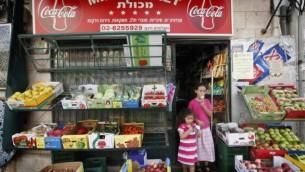 طفلتان تأكلان البوظة خلال مغادرتهما لميني ماركت في القدس، 2 أغسطس، 2010.  (Miriam Alster/Flash90)