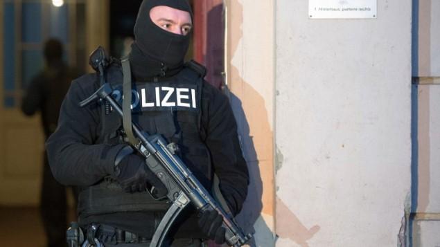 صورة للتوضيح: عنصر من الشرطة يقف أمام مبنى شقق سكينة حيت تم تنفيذ مداهمات ضد مشتبه بهم جهاديين في 16 يناير، 2015 في برلين. ( AFP/ LUKAS SCHULZE)