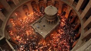 مصلون مسيحيون أرثوذكس يحملون الشموع التي أضاؤوها من 'النار المقدسة' مع احتشاد الآلاف في كنيسة القيامة في البلدة القديمة في القدس، 30 أبريل، 2016، خلال مراسم الاحتفال بعيد الفصح بحسب التقويم الشرقي. (AFP PHOTO / THOMAS COEX)