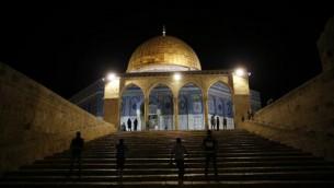 """فلسطينيون يمرون من أمام قبة الصخرة في مجمع المسجد الأقصى في الحرم القدسي خلال صلاة """"التراويح"""" في الليلة الأولى من شهر رمضان، في 6 يونيو، 2016. (Ahmad Gharabli/AFP)"""