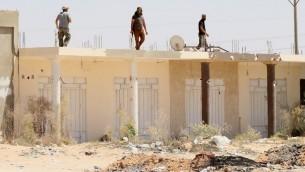 قوات موالية للحكومة الليبية فوق مبنى في مدينة سرت بعد السيطرة على احد احياء المدينة من تنظيم الدولة الإسلامية، 22 اغسطس 2016 (AFP PHOTO / MAHMUD TURKIA)