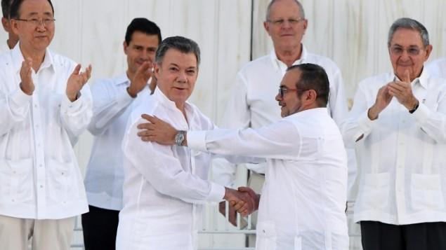 """الرئيس الكولومبي خوان مانويل سانتوس يصافح قائد حركة """"القوات المسلحة الثورية"""" (فارك) تيموشينكو خلال توقيع اتفاقية السلام التاريخية بين الحكومة الكولومبيا وفارك، 26 سبتمبر 2016 (LUIS ACOSTA / AFP)"""