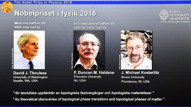 ثلاثة الحاصلين على جائزة نوبل الفيزياء للعام 2016، ديفيد ثاوليس وف. دانكن هولداين وج. مايكل كوستيرليتس، على الشاشة خلال مؤتمر صحفي للاعلان عن الفائزين في الكلية السويدية الملكية للعلوم في ستوكهولم، 4 اكتوبر 2016 (AFP PHOTO/JONATHAN NACKSTRAND)
