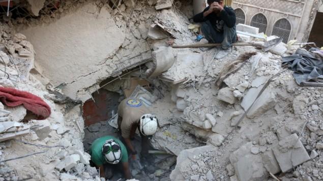 متوطعو الدفاع الوطني السوريين، المعروفين باسم الخوذ البيضاء، يبحثون عن ناجين بين حطام مباني بعد غارة جوية اجرتها قوات النظام على احد احياء حلب المحاصرة، 4 اكتوبر 2016 (AFP/Thaer Mohammed)