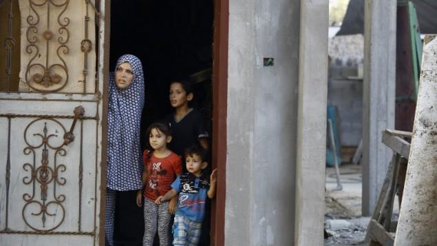 عائلة فلسطينية تطل من باب منزلها في حي الشجاعية شرقي مدينة غزة في أعقاب قصف إسرائيلي في 5 أكتوبر، 2016. (AFP/MOHAMMED ABED)