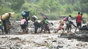 اشخاص يحاولون عبور نهرطافح في جنوب هايتي مع وصول الاعصار ماثيو، 5 اكتوبر 2016 (HECTOR RETAMAL / AFP)