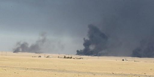 سحب الدخان تتصاعد من آبار النفط المشتعلة كما تظهر من قاعدة القيارة العسكرية، على بعد 60 كيلومترا من مدينة الموصل، في 16 أكتوبر، 2016، في الوقت الذي تستعد فيه القوات العراقية لشن عملية لإستعادة المدينة من تنظيم 'الدولة الإسلامية'، آخر معاقل التنظيم في العراق. (AFP PHOTO / AHMAD AL-RUBAYE)