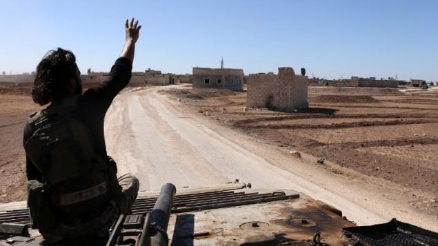 مقاتل من فصائل المعارضة السورية يجلس فوق عربة مدرعة خلال دخول القوات إلى قرية تلالين على المشارف الغربي لبلدة دابق السوري، في 16 أكتوير، 2016. (AFP PHOTO / Nazeer al-Khatib)