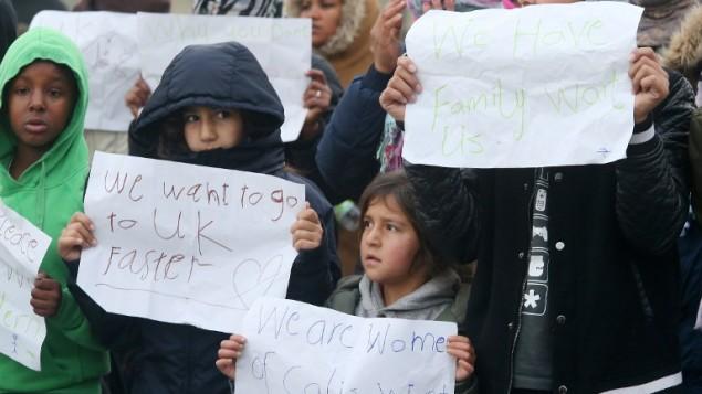 اطفال مهخاجرين يحملون لافتات تطالب بالذهاب الى بريطانيا في مخيم كاليه بشمال فرنسا، 26 اكتوبر 2016 (FRANÇOIS NASCIMBENI / AFP)