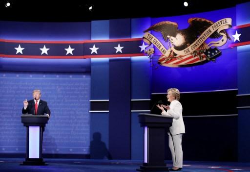 المرشحة الديمقراطية للرئاسة هيلاري كلينتون خلال المناظرة الرئاسية الثالثة والأخيرة مع المرشح الجمهوري دونالد ترامب (في الخلفية) في 'مركز توماس أند ماك' في  مدينة لاس فيغاس بولاية نيفادا، 19 أكتوبر، 2016. ( Win McNamee/Getty Images/AFP)