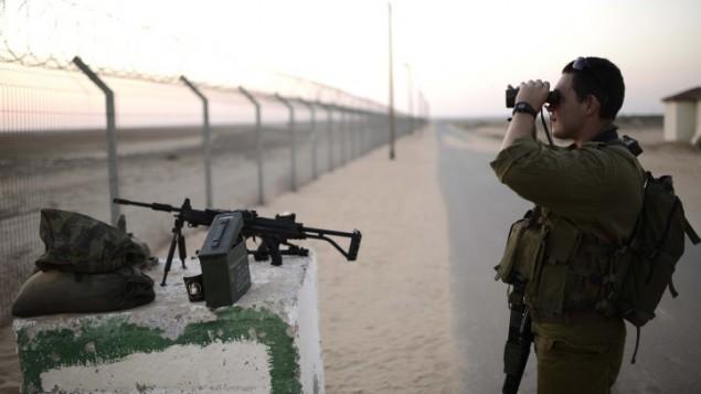 صورة توضيحية: جندي إسرائيلي من الفرقة العاشرة ينظر عبر ناظور إلى قطاع غزة من بلدة إسرائيلية قريبة، 7 أغسطس، 2014.  (Tomer Neuberg/ Flash90)