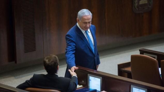 رئيس الوزراء بينيامين نتنياهو وزعيم المعارضة يتسحاق هرتسوغ يتصافحان خلال جلسة خاصة للكنيست للإحتفال بالذكرى الخمسين لإنشاء البرلمان الإسرائيلي، 19 يناير، 2016. (Yonatan Sindel/Flash90)