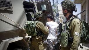 صورة توضيحية: القوات الإسرائيلية تعتقل فلسطينيا بعد إلقاءه زجاجة حارقة، كما زُعم، في مدينة الخليل في الضفة الغربية، 1 يونيو، 2016. (Wisam Hashlamoun/Flash90)