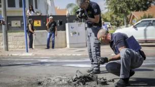 خبيرو المتفجرات في الشرطة الإسرائيلية يستخرجون قطعة من صاروخ تم إطلاقه من قطاع غزة وسقط في وسط شارع في مدينة سديروت الإسرائيلية، 5 أكتوبر، 2016. (FLASH90)