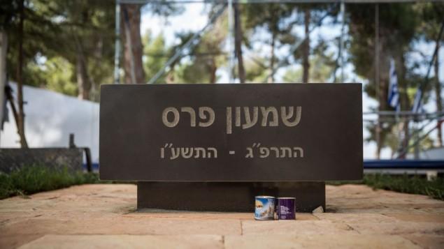 شموع تذكارية أمام شاخد قبر شمون بيرس في مقبرة جبل هرتسل في القدس، 27 أكتوبر، 2016، قبل يوم من مراسم إزاحة الستار لإحياء ذكرى مرور شهر على وفاته. (Hadas Parush/Flash90)