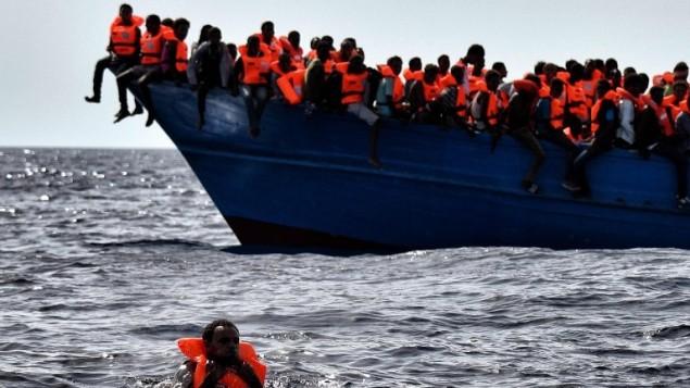 توضيحية: مهاجرون ينتظرون الانقاذ على متن زورق يبعد حوالي 20 ميل بحري عن شواطئ ليبيا، 3 اكتوبر 2016 (AFP/Aris Messinis)