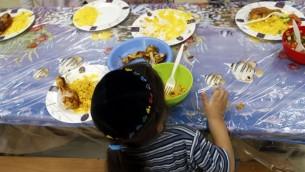 طفل يهودي يأكل في مركز ياد عزرا فاشلوميت في القدس، الذي يقدم وجبات غذاء ساخنة يوميا لاكثر من 1,200 طفل تحت خط الفقر، 27 سبتمبر 2011 (Uri Lenz/FLASH90)