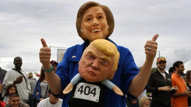 امرأة ترتدي قناع هييلاري كلينتون تحمل دمية للمرشح الجمهوري دونالد ترامب خلال مسيرة بمناسبة الهالوين في كاليفورنيا، 30 اكتوبر 2016 (AFP / Mark RALSTON)