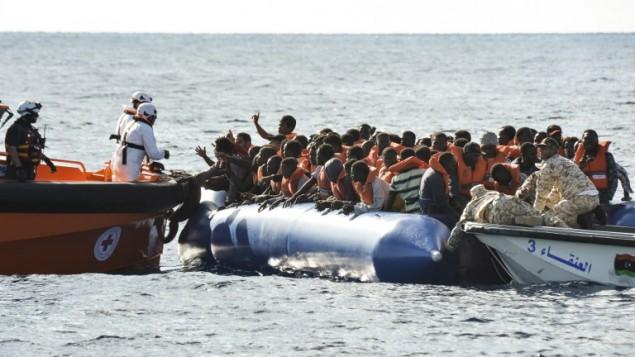 مهاجرون ولاجئون يجلسون في قارب مطاطي خلال عملية إنقاذ ل'توباز رسبوندر'، قارب إنقاذ تديره منظمة Moas غير الحكومية المالطية والصليب الأحمر الإيطالي بمساعدة خفر الساحل الليبي قبالة السواحل الليبية، 4 نوفمبر، 2016.  (AFP PHOTO / ANDREAS SOLARO)