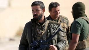 عنصر من 'قوات سوريا الديمقراطية' يحمل معه قاذفة قنابل في الوقت الذي يحتشد هو ورفاقه في بلدة عين عيسى، على بعد 50 كيلومترا شمال الرقة، 6 نوفمبر، 2016. (AFP PHOTO / DELIL SOULEIMAN)