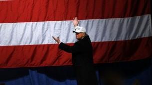 المرشح الجمهوري للانتخابات الامريكية دونالد ترامب ينظر الى العلم الامريكي بعد مخاطبته داعميه في مدرج فريدوم هيل في ولاية مشيغن، 6 نوفمبر 2016 (AFP/ JEFF KOWALSKY)