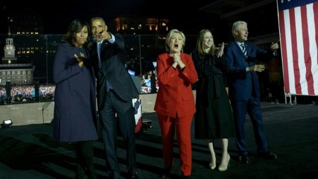 السيدة الأولى ميشيل أوباما (من اليسار) والرئيس الأمريكي باراك أوباما (الثاني من اليسار) والمرشحة الديمقراطية للرئاسة هيلاري كلينتون (وسط الصورة) وتشلسي كلينتون (الثانية من اليمين) وبيل كلينتون (من اليمين) يحيون الجمهور خلال مهرجان إنتخابي في 'إندبندنس مول'، 7 نوفمبر، 2016 في فيلادلفيا، بنسلفانينا. (AFP PHOTO / Brendan Smialowski)