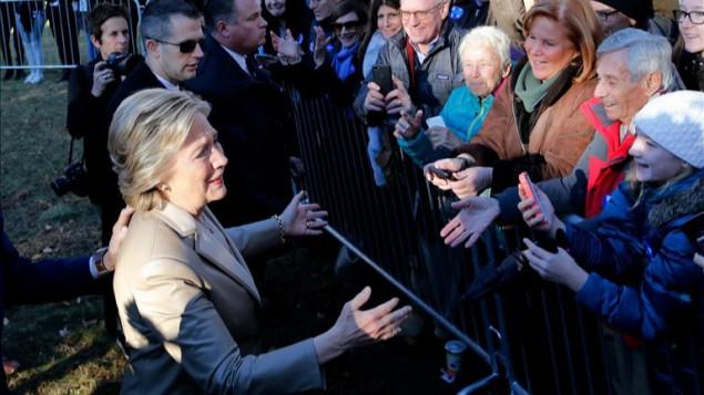 المرشحة الديمقراطية هيلاري كلينتون تحيي بداعميها بعد الادلاء بصوتها في نيويورك، 8 نوفمبر 2016 (Eduardo Munoz Alvarez/AFP)