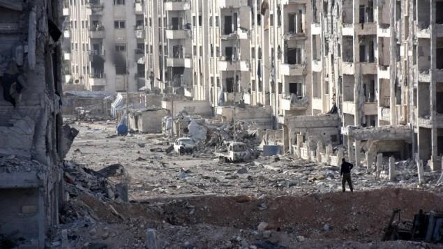 عناصر من القوات الموالية للنظام السوري تقف وسط مبان تضررت بشكل كبير في منطقة '1070 شقة' في 8 نوفمبر، 2016، بعد أن إستعادتها من عناصر المتمردين. ( AFP PHOTO / GEORGES OURFALIAN)