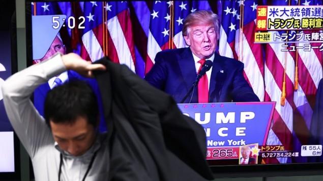 موظف ياباني يغادر مكان عمله في شركة تداول أسهم في طوكيو في 9 نوفمبر، 2016، وفي الخلفية يظهر الرئيس الأمريكي المنتخب دونالد ترامب خلال إلقائه خطاب الفوز. (AFP PHOTO / BEHROUZ MEHRI)